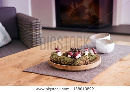 closeup of wooden table with decor in living room with fireplace in the background