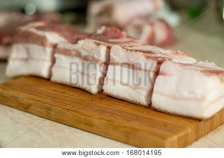 lard lying on a cutting board sliced into rectangles