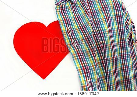 Closeup of T-shirt with a red heart on a white background under colorful checkered unbuttoned shirt