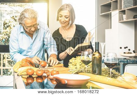 Senior couple cooking healthy food and drinking red wine at house kitchen - Retired people at home preparing lunch with recipe book about bio vegetables - Happy elderly concept with mature pensioner