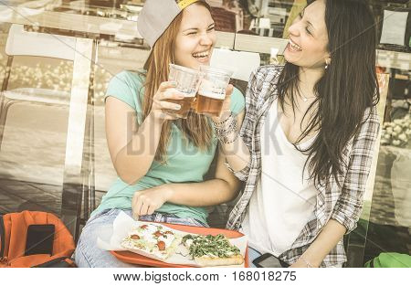 Young women eating pizza and drinking beer at bar restaurant outdoors - Friendship concept with happy girlfriends having fun moments together - Pretty girl friends on retro desaturated vintage filter