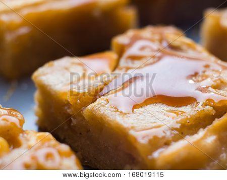 Home made apple cinnamon blondies with salted caramel. Sweet food dessert macro detail