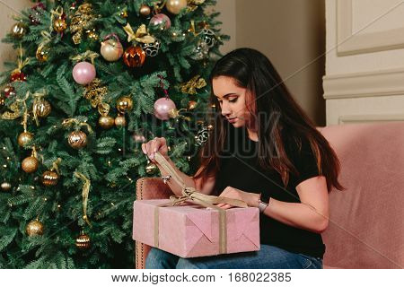Beautiful young brunette woman on a sofa unpacks the gift near the Christmas tree. Studio horizontal portrait