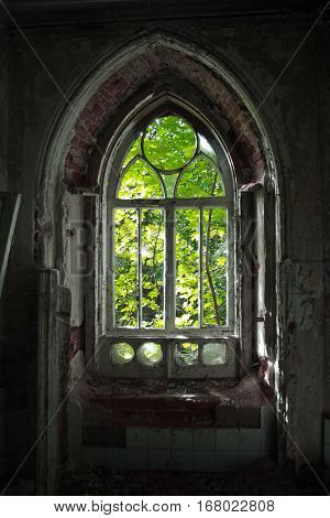 Old rotten window with the remnants of stained glass of an abandoned mansion of Khvostov in gothic style, Lipetsk region