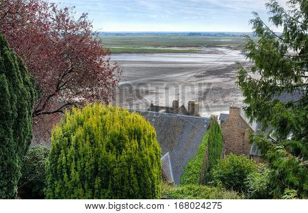 Spectacular top view on green trees and tidal causeway in Mont-Saint-Michel, Normandi France