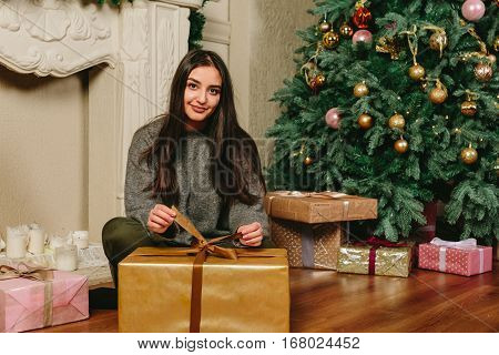 Beautiful young brunette girl sitting on the floor and unpacks the gift near a Christmas tree. Studio horizontal photo.