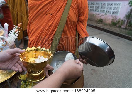Buddhist putting food into a Buddhist monk's bowl.