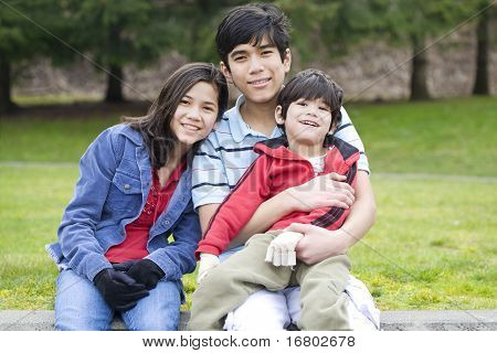 Children Taking Care Of Disabled Brother At Park