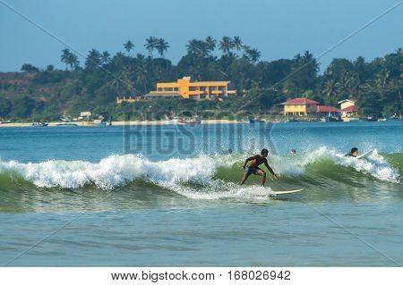 Weligama, Sri Lanka - January 09 2017: Unidentified Man Surfing On A Large Wave On Weligama Beach On