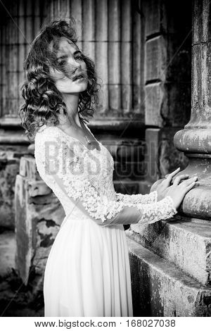 Beautiful fashion model in luxurious white dress on a city street. Charming bride woman walking down the street. Beauty, fashion. Black-and-white portrait.