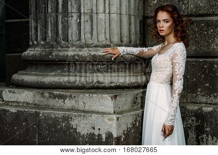 Beautiful fashion model in luxurious white dress on a city street. Charming bride woman walking down the street. Beauty, fashion.
