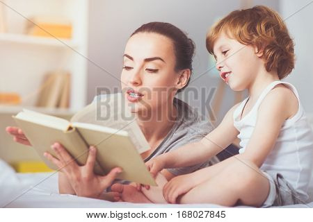 Listen to a story. Delighted pretty young mother reading a fairytale to her toddler son and smiling while enjoying the time with family.