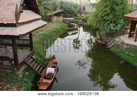 Thai wooden house and boat in the canel