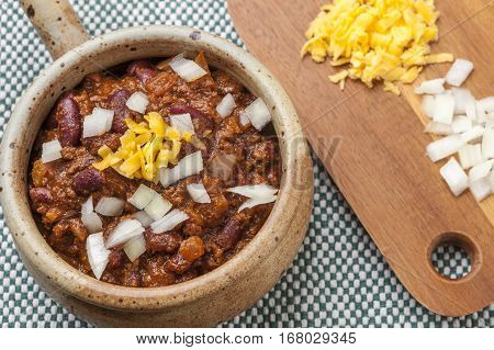 Chili topped with cheese and onions by a cutting board.