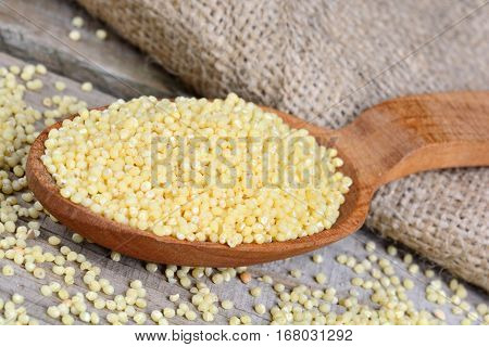 Millet seeds in a spoon and jute canvas on wooden table