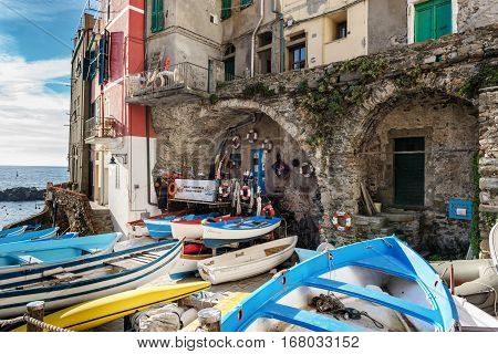 RIOMAGGIORE, ITALY - DECEMBER 2016: Closed boat rental office and moored boats at coast of Riomaggiore town, Italy