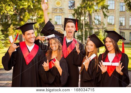Excited Successful Five Graduates In Robes Standing In Row And Showing Certificate