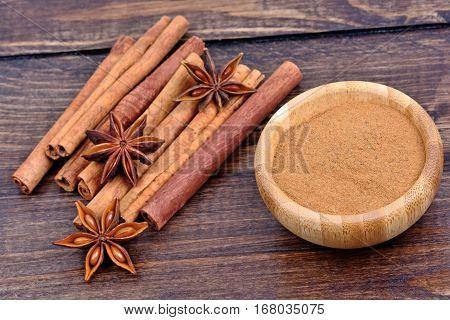 Cinnamon sticks with star anise and cinnamon powder on table