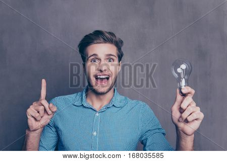 Portrait Of Young Smart Man With Idea Holding Lamp And Gesturing With Finger