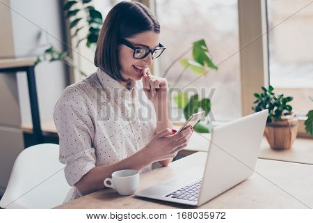 Attractive Happy Woman With Laptop Reading Sms In Office