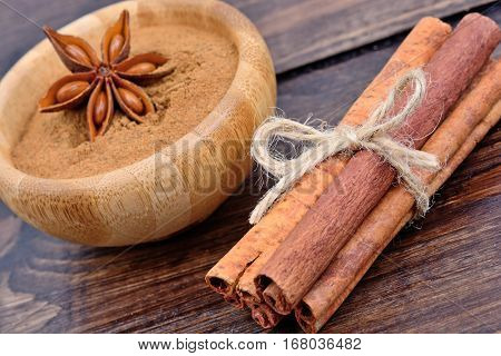 Cinnamon sticks and bowl with cinnamon powder on wooden table