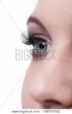 Close up of single human female blue eye with long dark lashes and one nose on white background
