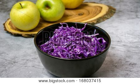 Shredded Red Cabbage With Apples In Black Bowl On Grey Background. Vegetarian Healthy Food. Top View