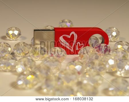 Red flash drive with heart and gems on the light background