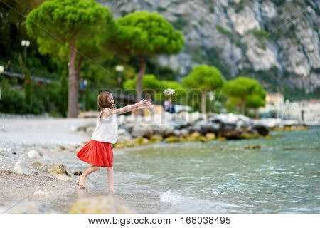 Two Cute Little Sisters Having Fun On A Beach Of Limone Sul Garda, A Small Town And Comune In The Pr