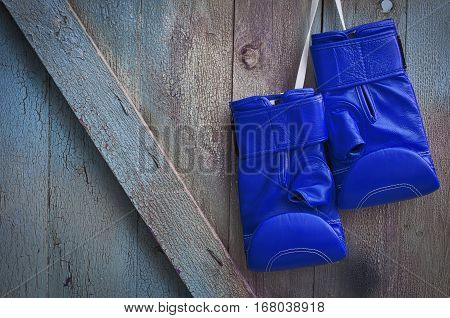 Blue leather boxing gloves hanging on a cord on a nail white blue wooden wall with cracked paint