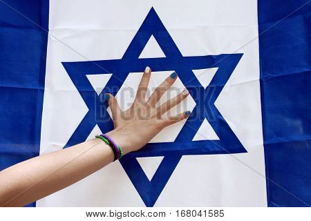 Maiden's hand with a blue-white manicure against the backdrop of the Israeli flag