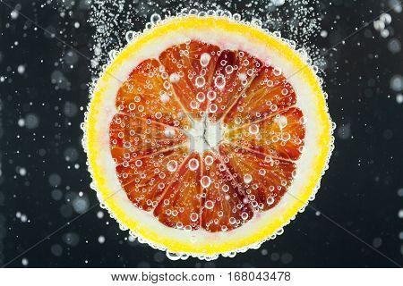 Orange Citrus Slice Falling Into Water