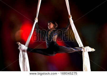 Young woman circus air gymnast. On black background