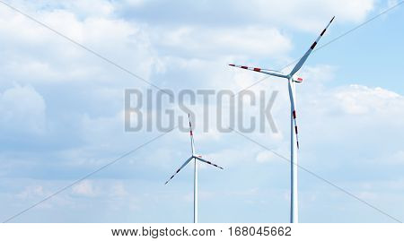 Electric wind turbines on blue sky background. Green energy background. Wind power plants close up. Free space for text on blue sky background.