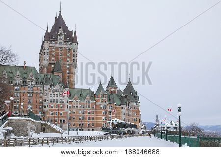 View of Frontenac Castel (Chateau de Frontenac, in French) in winter under the snow. The Chateau Frontenac is a grand hotel in Quebec City, Quebec, Canada, and a symbol of the city