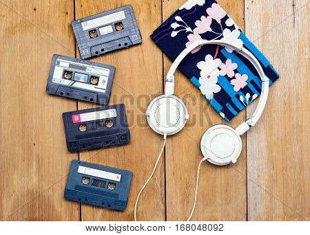 Top View Cassette Tape And Head Phone Laying On Wood Board