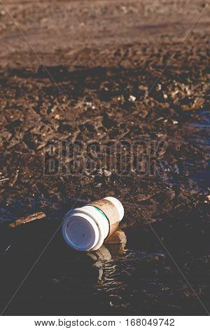 Starbuck Coffee Cup In Muddy Puddle