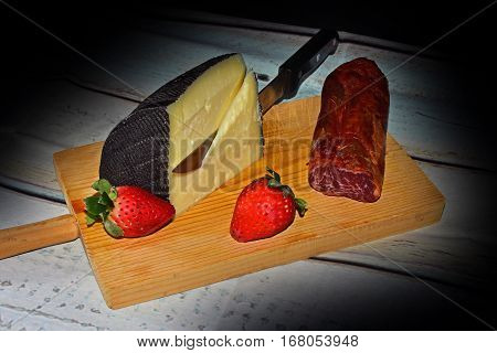 still life with cheese, loin and strawberries