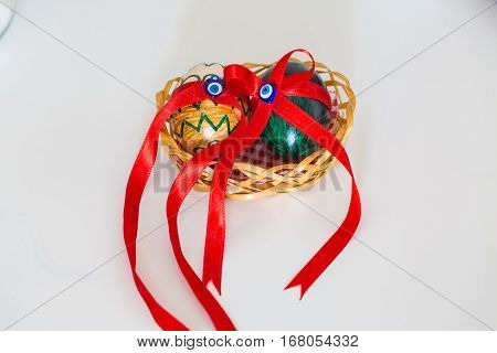 Two painted eggs with evil eye on a basket with red ribbons.