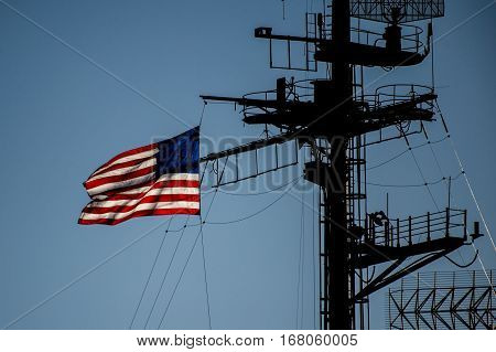 American flag flying on the communications mast of a navy ship