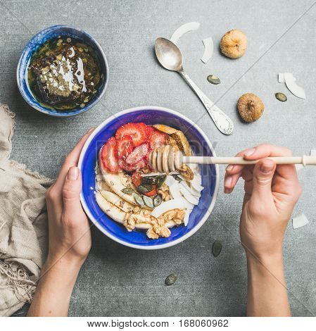 Healthy breakfast bowl. Yogurt, granola, seeds, fresh and dry fruits and honey in blue ceramic bowl in woman' s hands over grey background, top view, square crop. Clean eating, dieting food concept