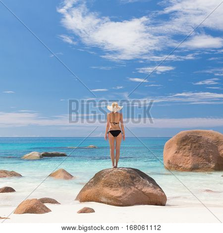 Woman wearing black bikini and beach hat, enjoying amazing view on Anse Lazio beach on Praslin Island, Seychelles. Summer vacations on picture perfect tropical beach concept.