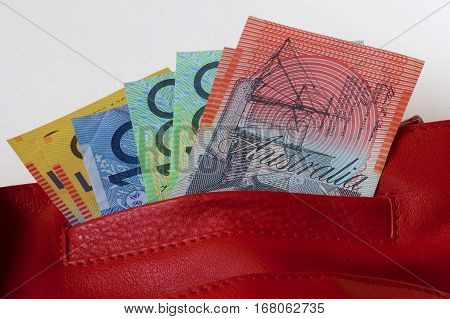 An assortment of Australian dollar notes in the pocket of a red leather bag.
