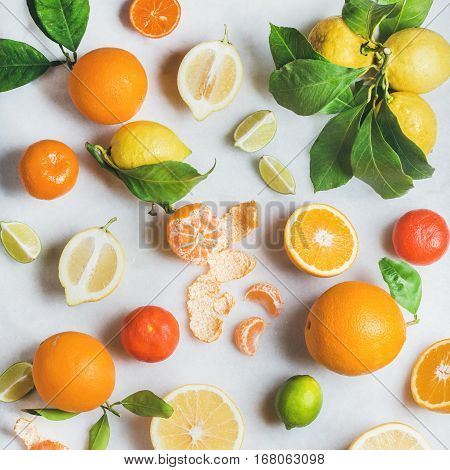 Variety of fresh citrus fruits for making juice or smoothie over light grey marble table background, top view, square crop. Healthy eating, vitamin, detox, diet food, clean eating concept