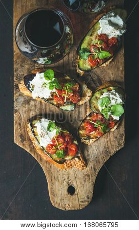 Wine and snack set. Brushetta with grilled eggplant, cherry tomatoes, garlic, cream cheese, arugula and glass of red wine on wooden board over dark background, top view. Slow food, party food concept