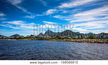 Cityscape view of Guanabara Bay and embankment at sunny day with blue sky, white spindrift clouds and Christ the Redeemer on the background in the city of Rio De Janeiro, Brazil