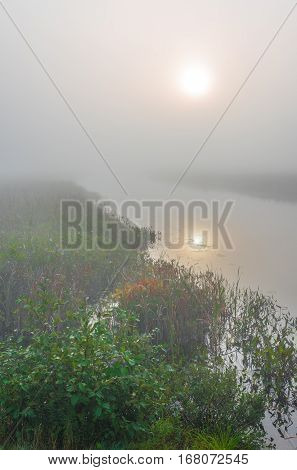 Brilliant & bright mid-summer sunrise on a narrow passage of a lake.   Warm water & cooler air at daybreak create local misty fog.