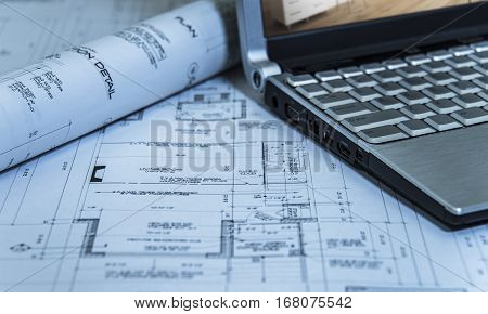 architects roll of 2d modern new house plan with laptop, 2ds of a new house construction plans on builders desk, close up of house plans with computer, house plan blueprints for a new housing development