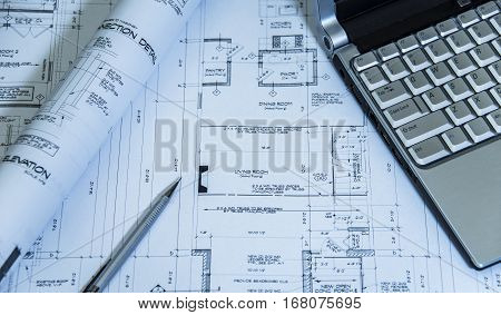 Architectural blueprints of three story house, with laptop, pencil and remodeling plan