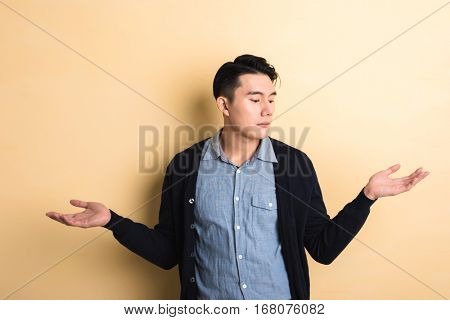 young man give you a helpless sign , shot at studio yellow background